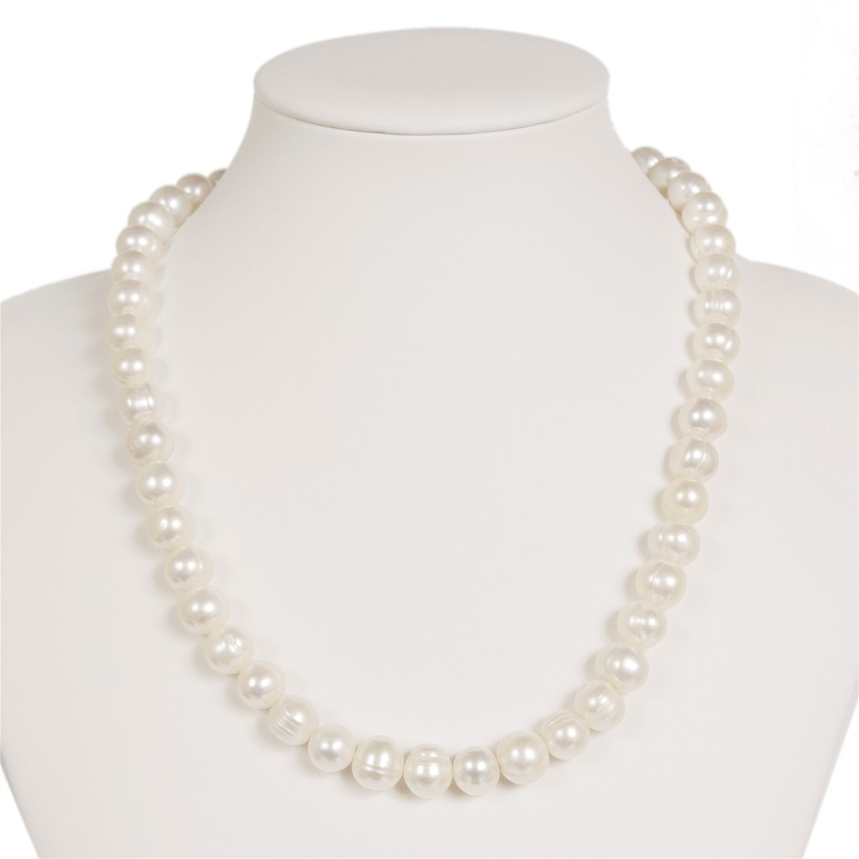 Single Strand Of Off Round Freshwater Pearls On White Silk.